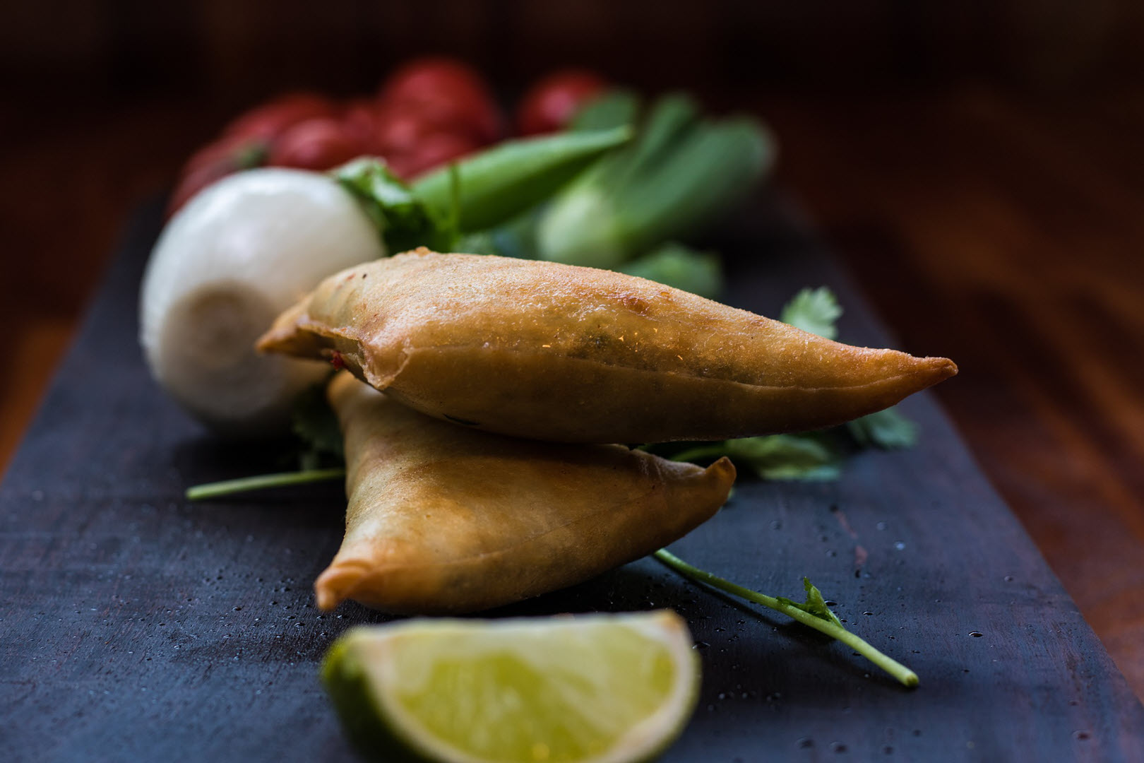 Indian samosas on a wooden serving board next to an onion and red pepper
