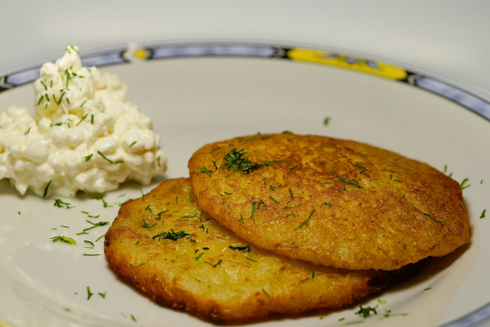 two fried potato pancakes on a plate with sour cream