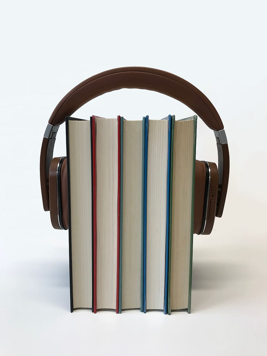 brown headphones placed around several standing books