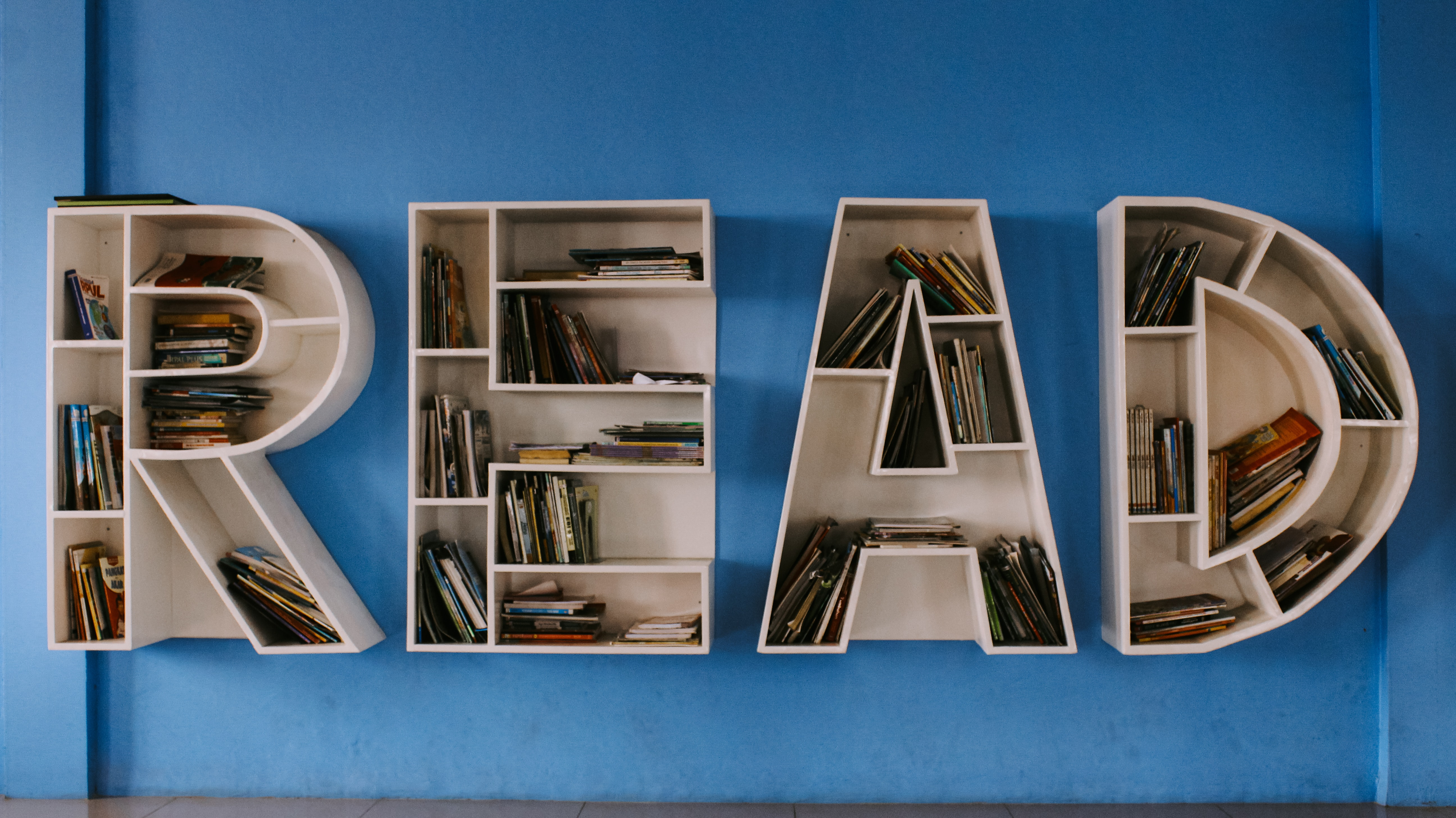 """Shelves in the shape of letters that spell """"Read"""" with books inside each letter on a blue wall"""