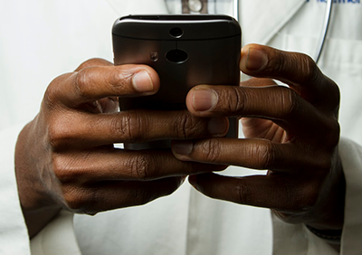 Photograph zoomed in on a pair of hands holding a mobile phone