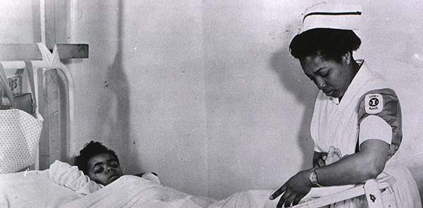 Historical image of African American nurse treating a child in the hospital