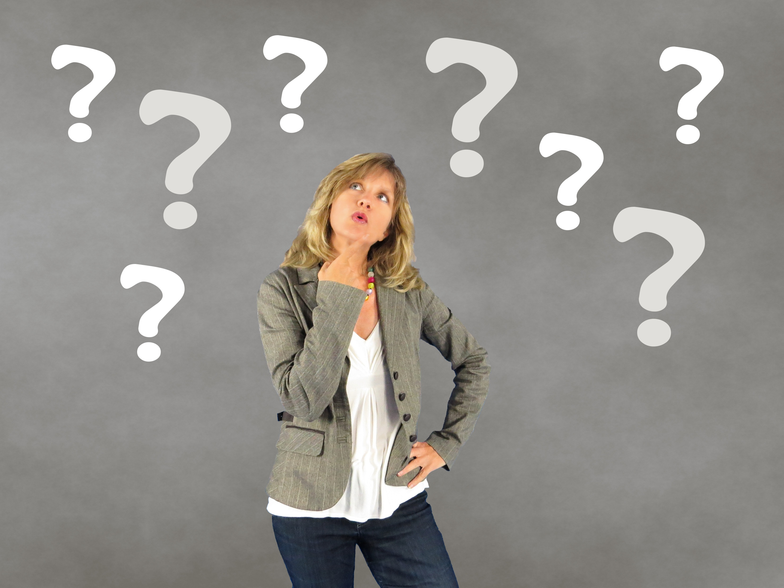 Woman with hand on her chin surrounded by question marks