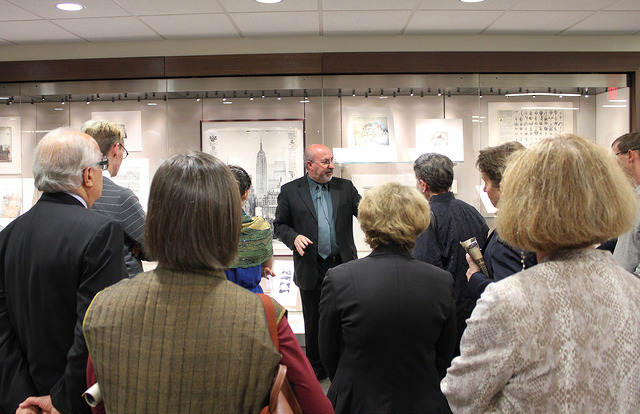 Erik Denker, Senior Lecturer at the National Gallery of Art, giving a talk in front of a Booth Special Collections exhibit