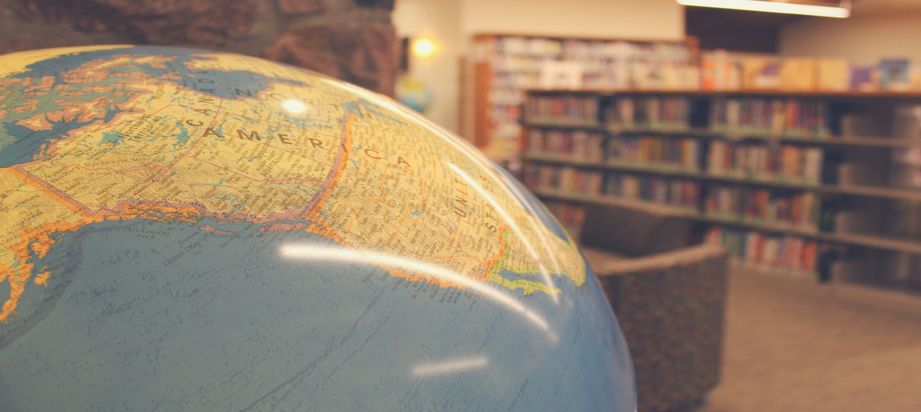 Photo of lighted globe with library shelves in the background.