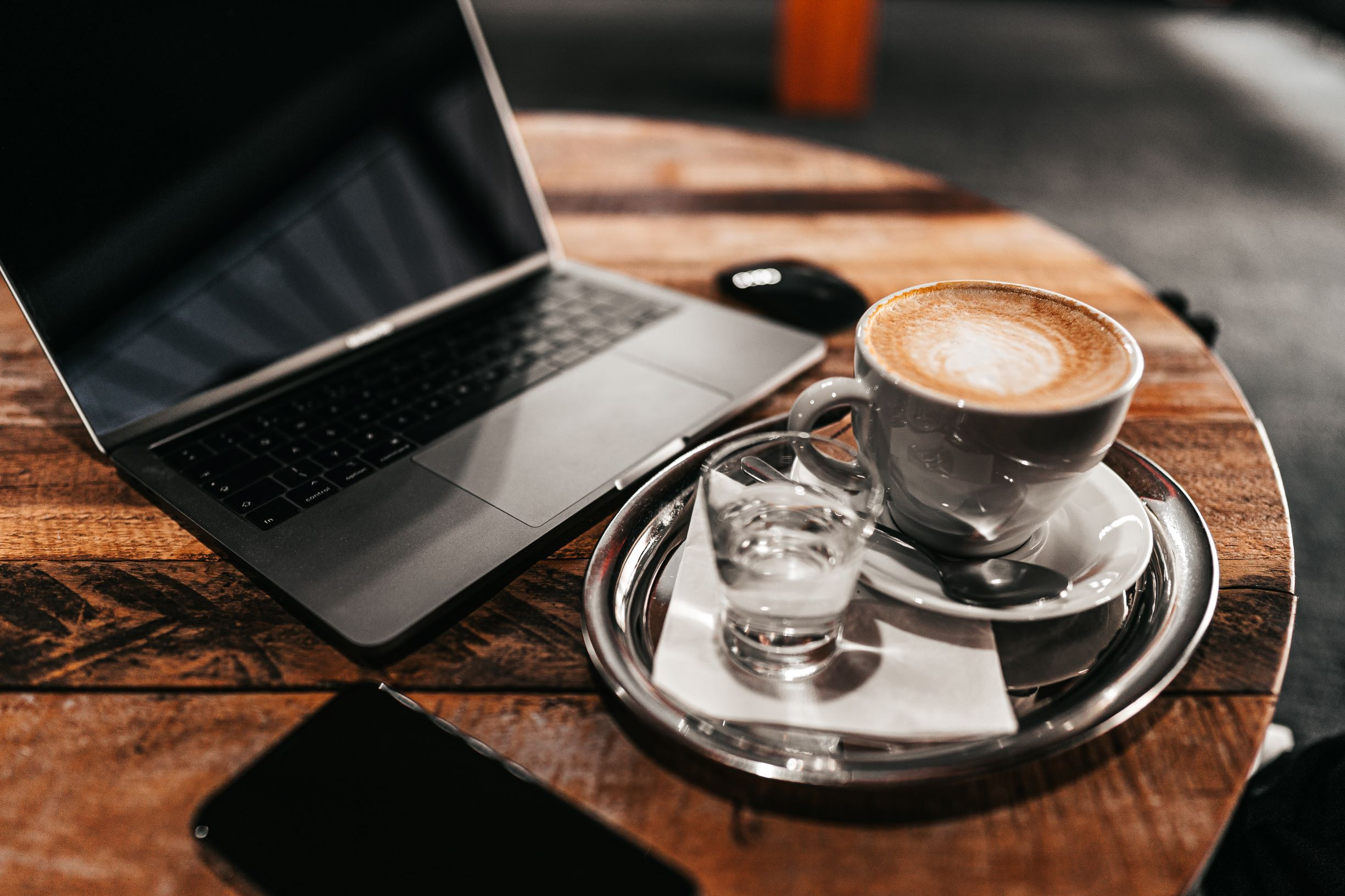 laptop and a cappuccino on wood table
