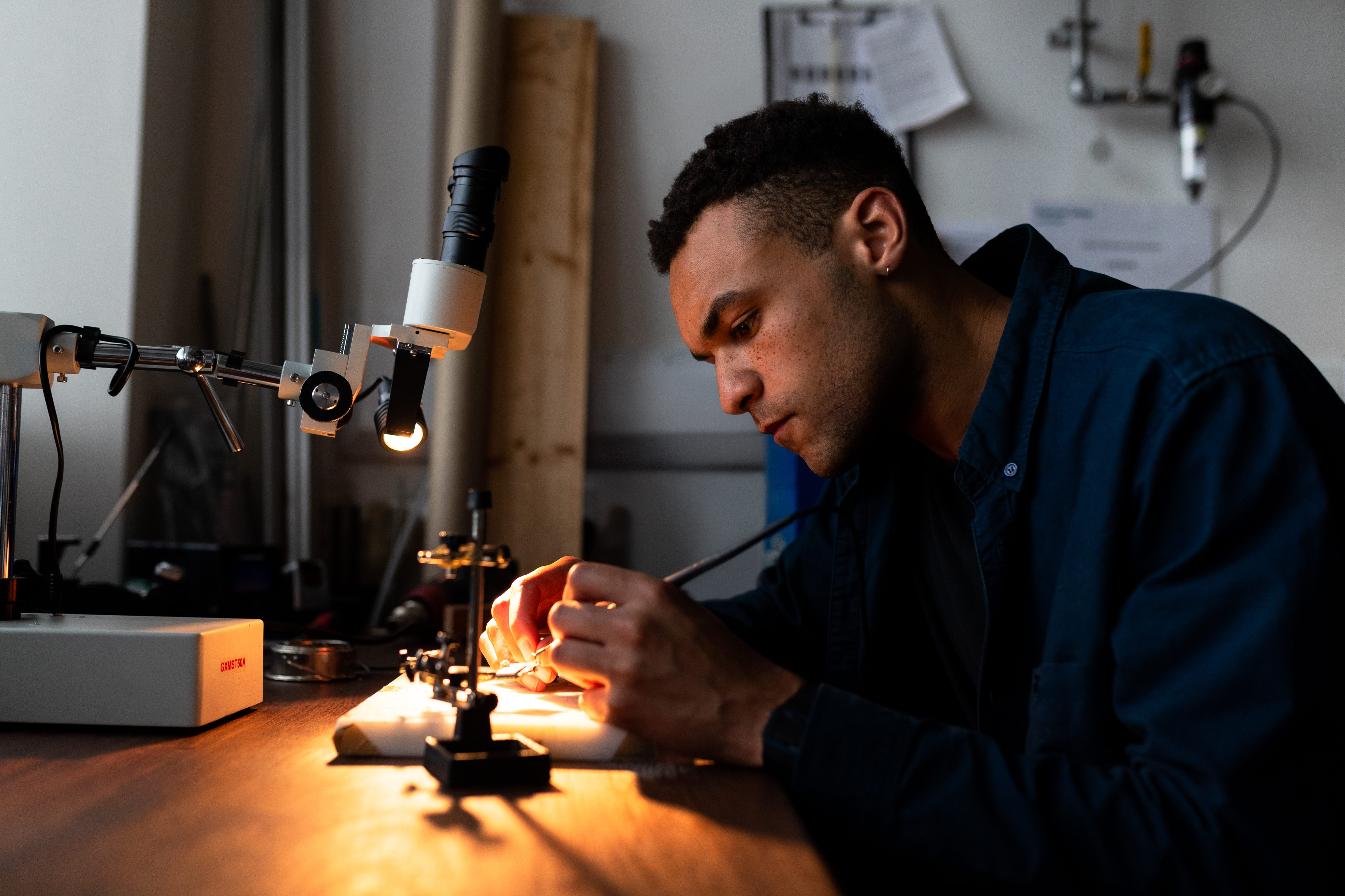 Male mechanical engineer solders parts for prosthetic limbs
