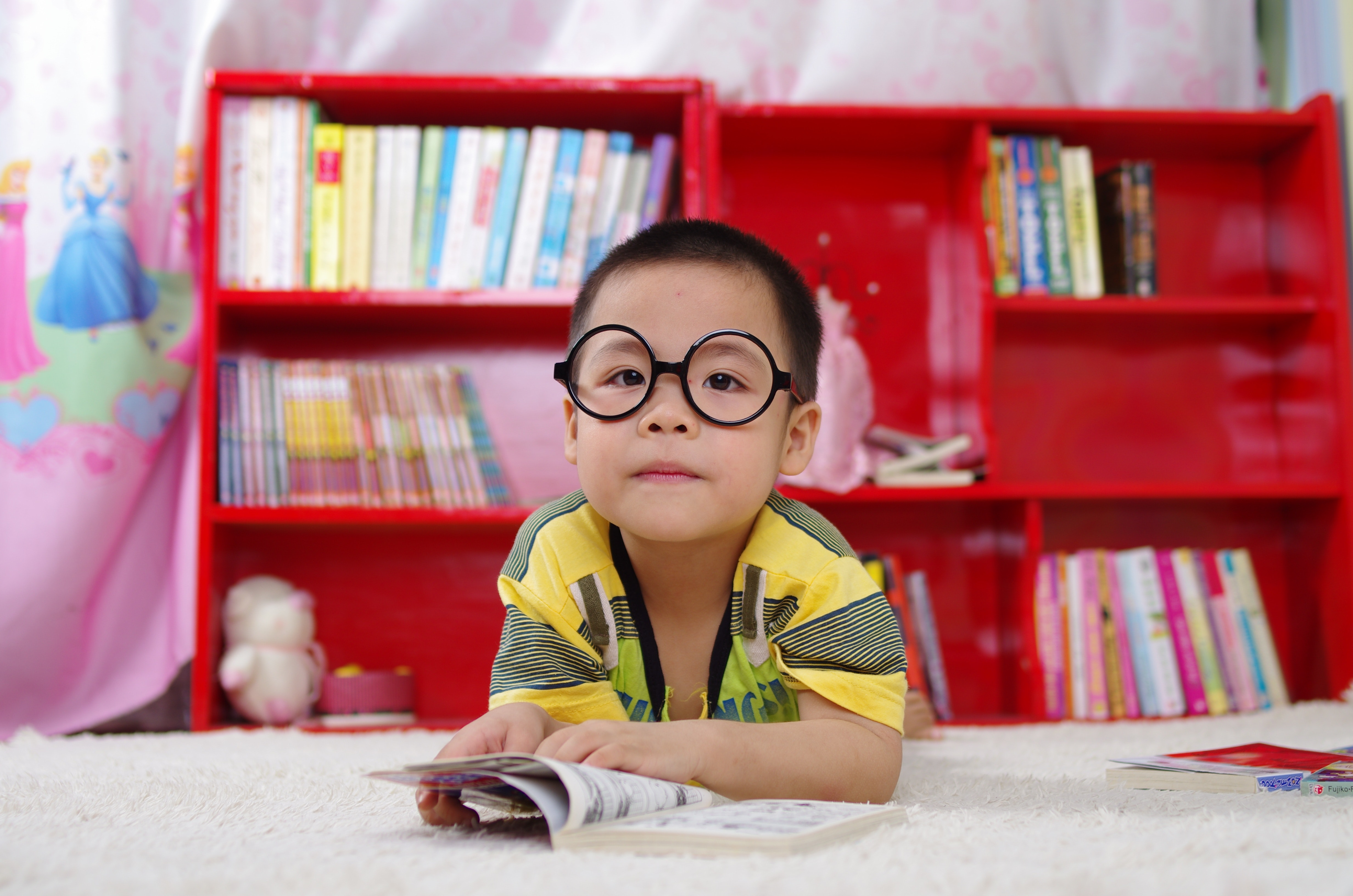Child reading a book in front of a bookcase.