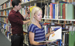 students looking at books in the library