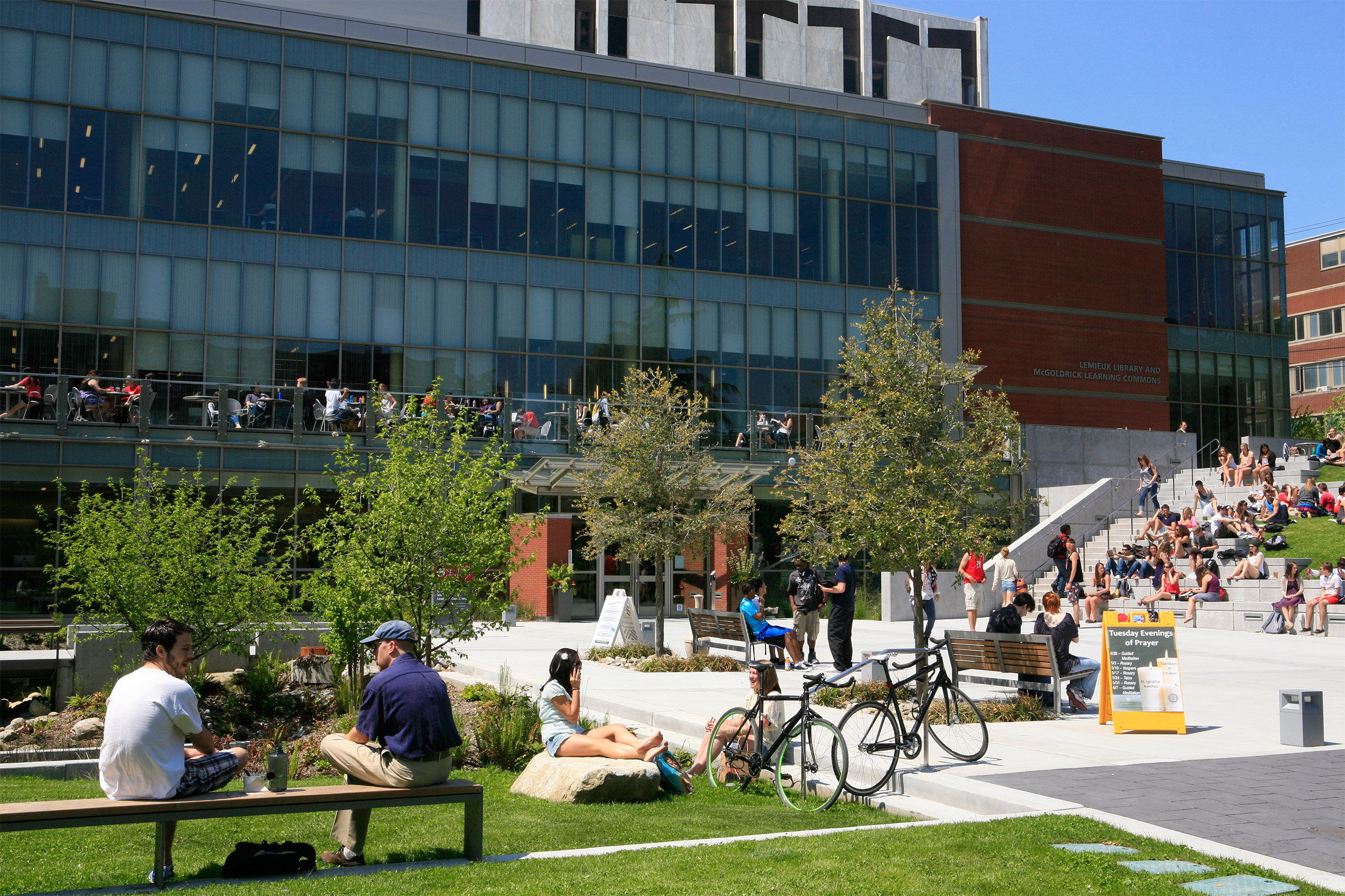 photograph of outdoor plaza behind Lemieux Library, with students seated on lawn and stairway.