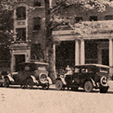 Two 1920s era cars parked in front of a campus building