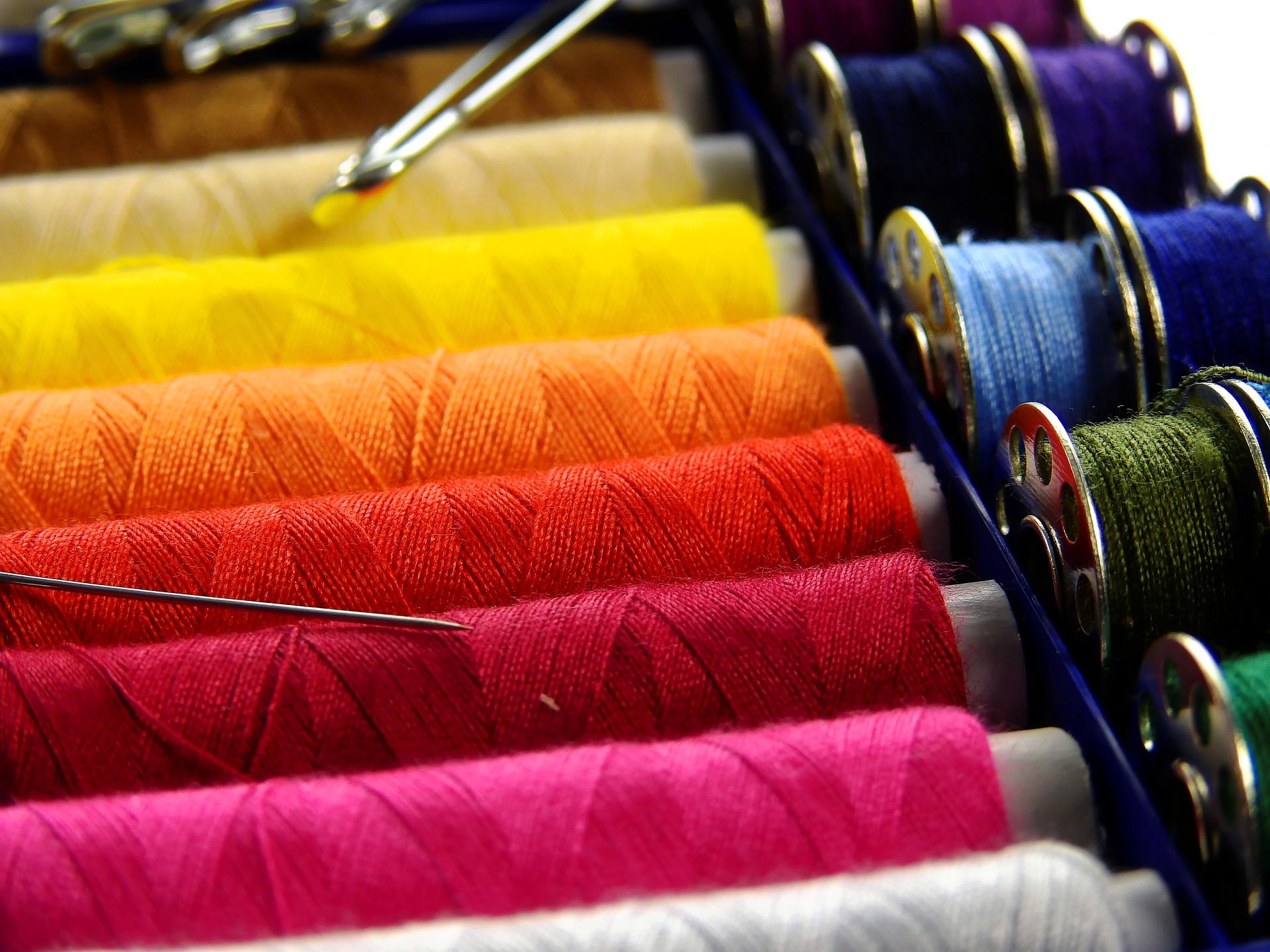 Image of multi-colored threads on bobbins.