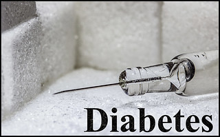 Insulin syringe setting on top of sugar cubes.