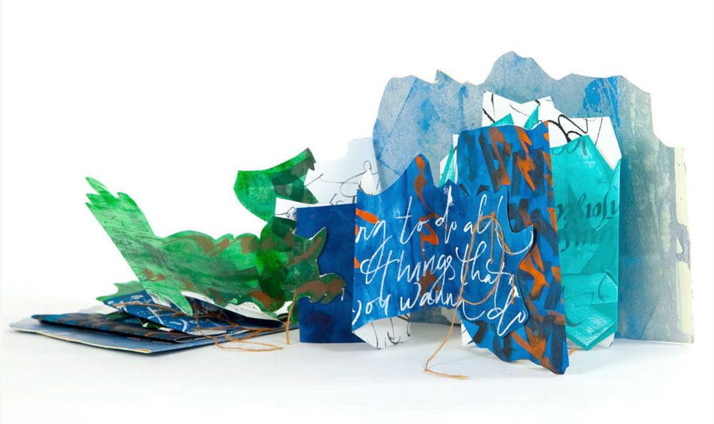 "Image of artists' book ""Finding Myself"" - depicts a book partially unfolded with blue-green pages, covered in handwritten text"