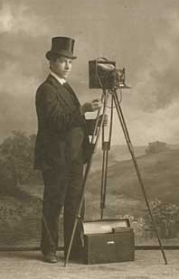 Ole Aarseth posed with camera and equipment, studio portrait, 1901-1902.