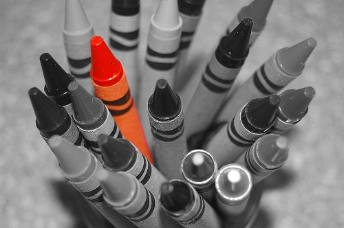 A collection of crayons in black and white with one orange crayon standing out among them.