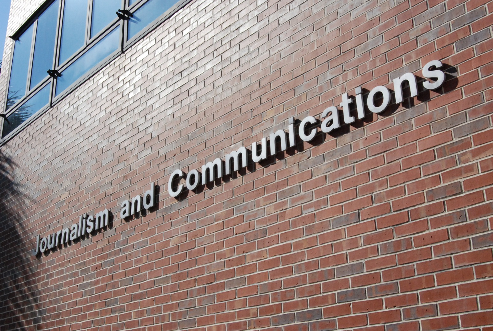 Journalism and Communications sign on red brick wall