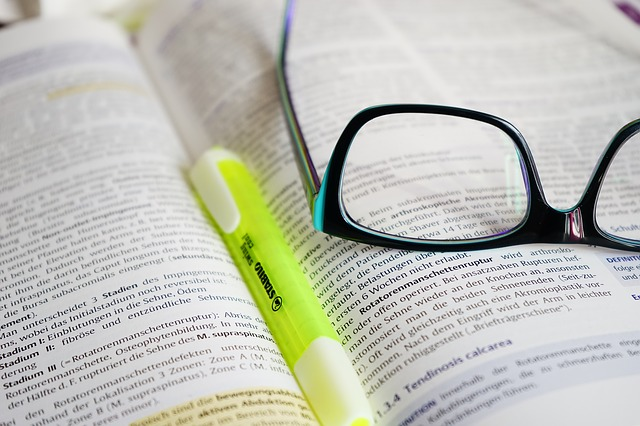 Book with reading glasses and highlighter