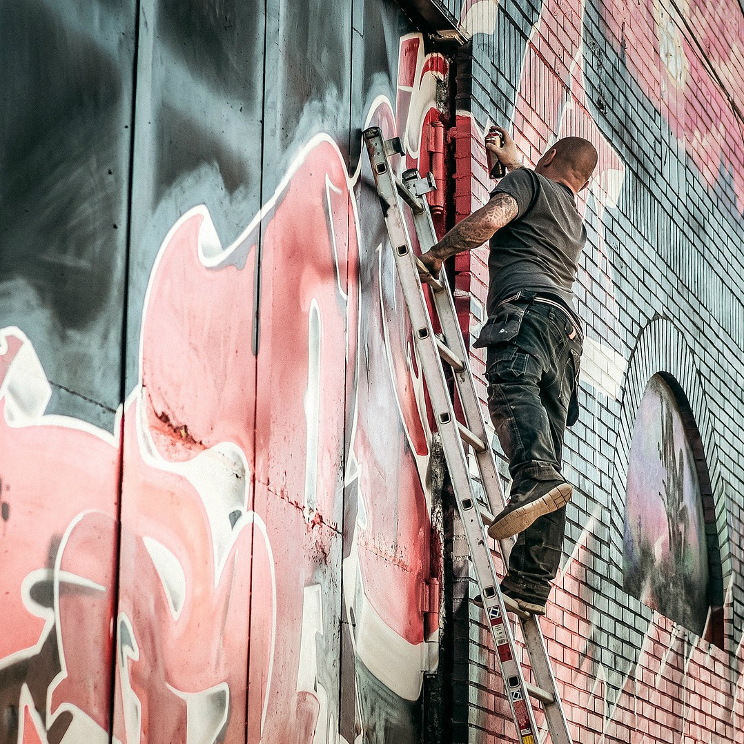 Muriel artist on ladder, spray-painting wall; what is being painted is unclear from the photo, as it appears to be either impressionistic shapes or graffiti tags