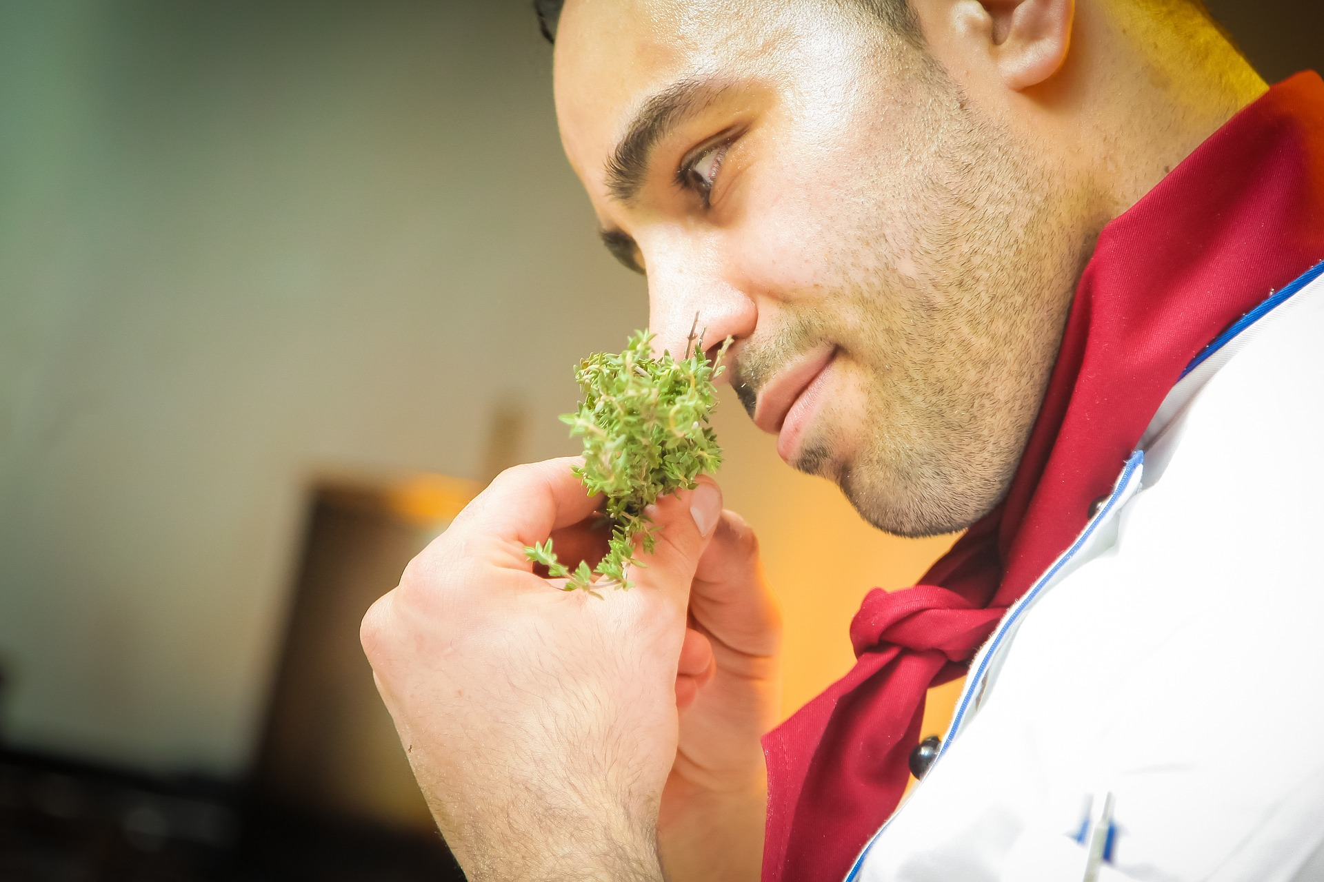 chef wearing red scarf sniffing a small bunch of green herbs