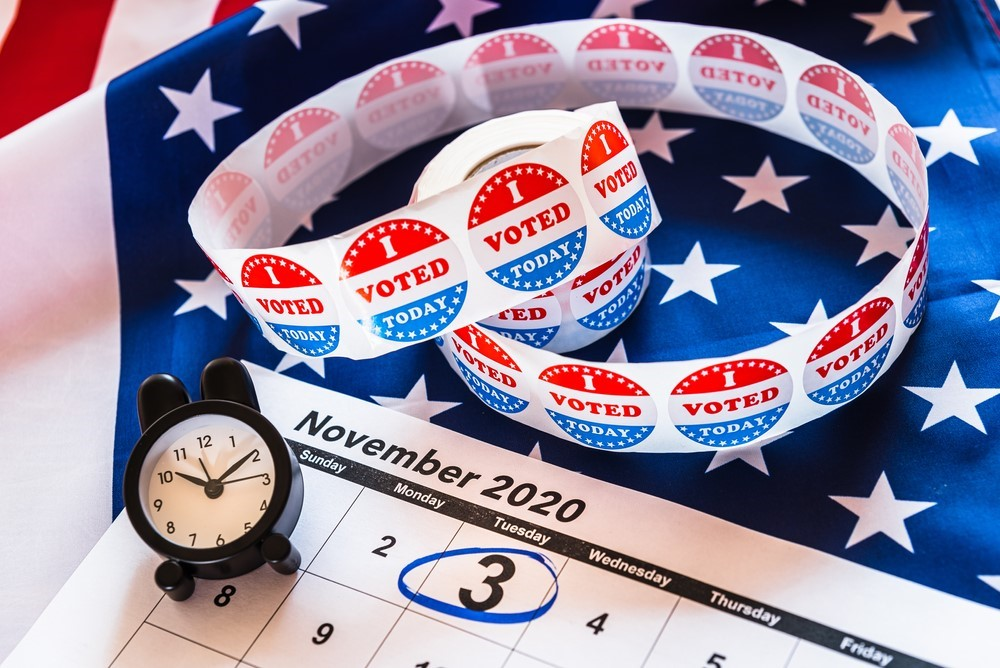 I Voted stickers and an alarm clock arranged around a calendar for November 2020. 3rd of November is circled.