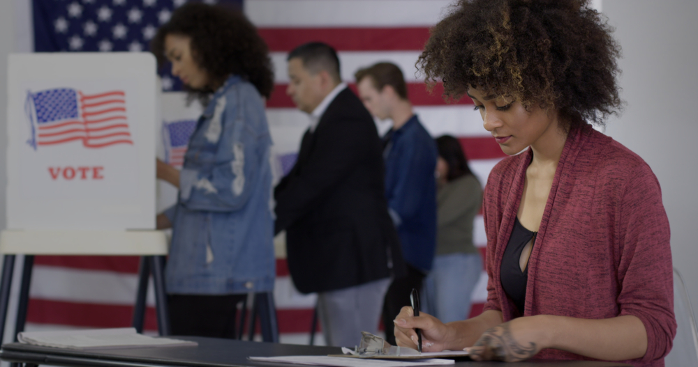 A young woman fills out a form while people vote in the background.