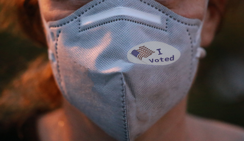 """Person wearing a mask over their nose and moth with an """"I voted"""" sticker on the mask"""