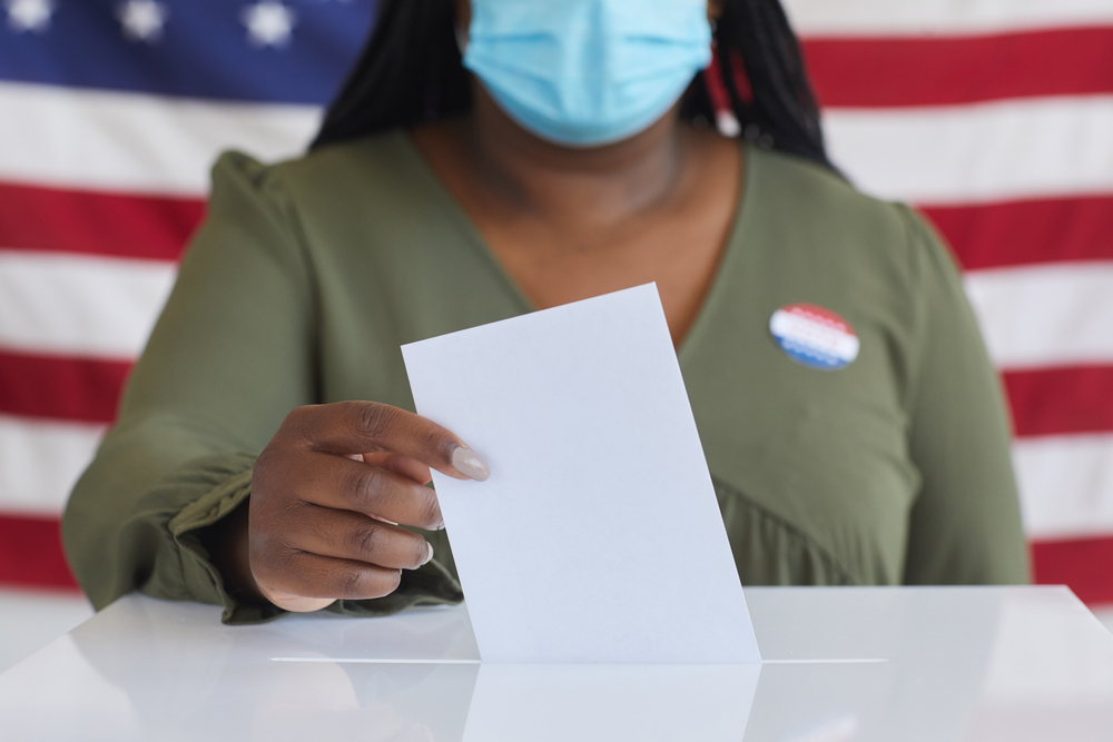 Black woman wearing a surgical mask drops a paper ballot into a box.