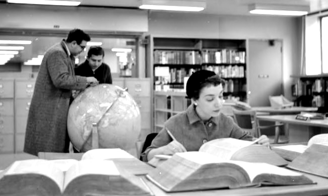 Woman in library reading a large book while two men examine a globe.