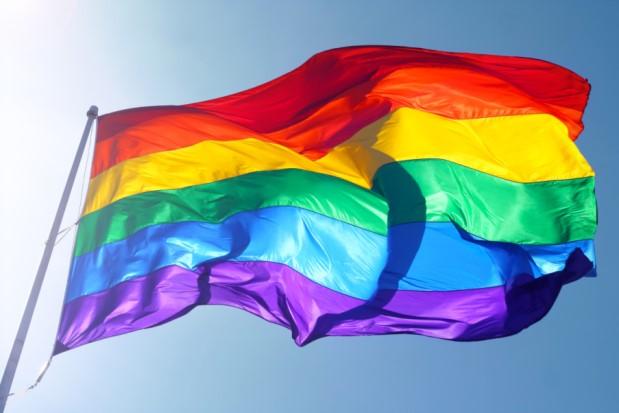 rainbow pride flag flutters against a blue sky