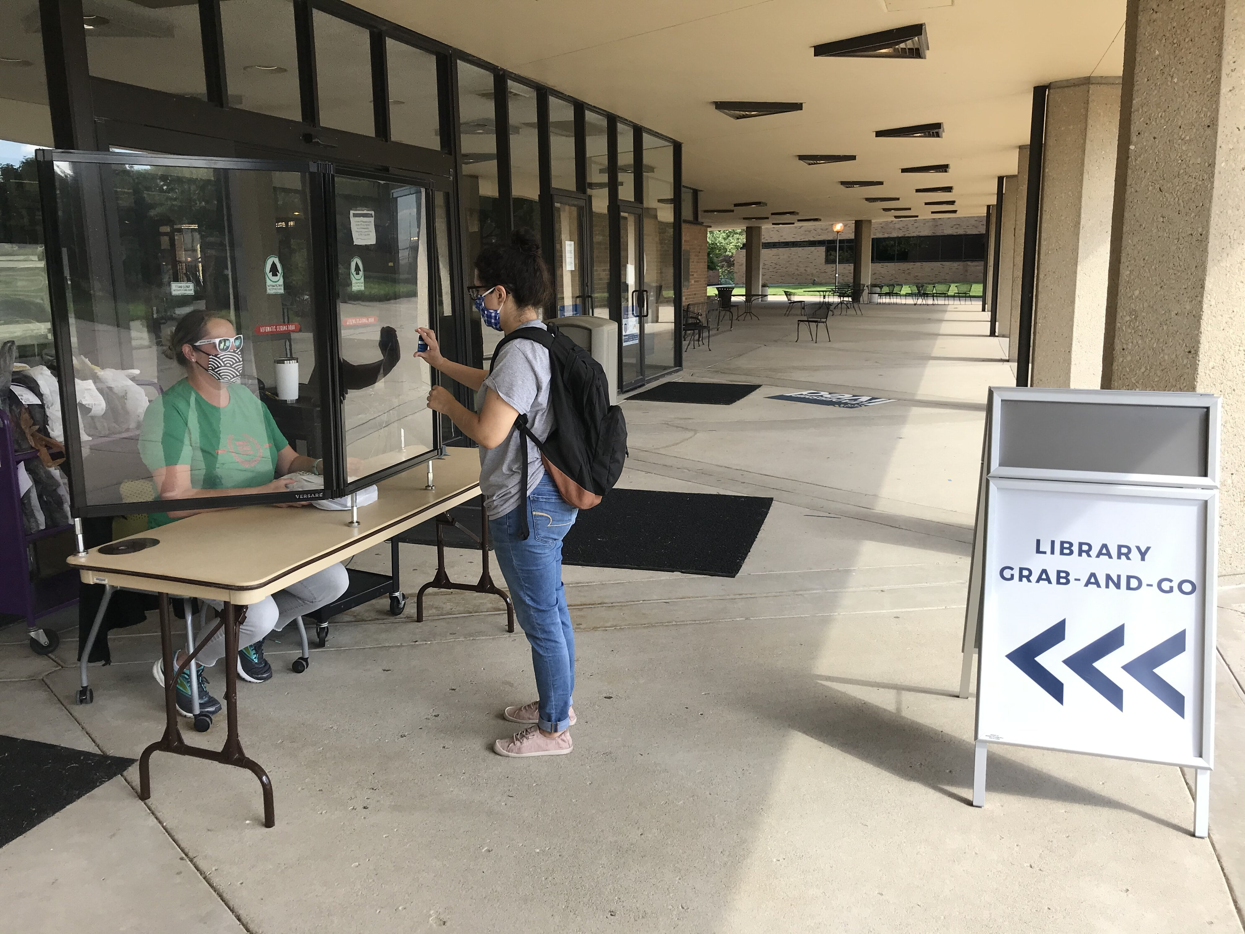 Student collecting items from grab and go table outside of the library