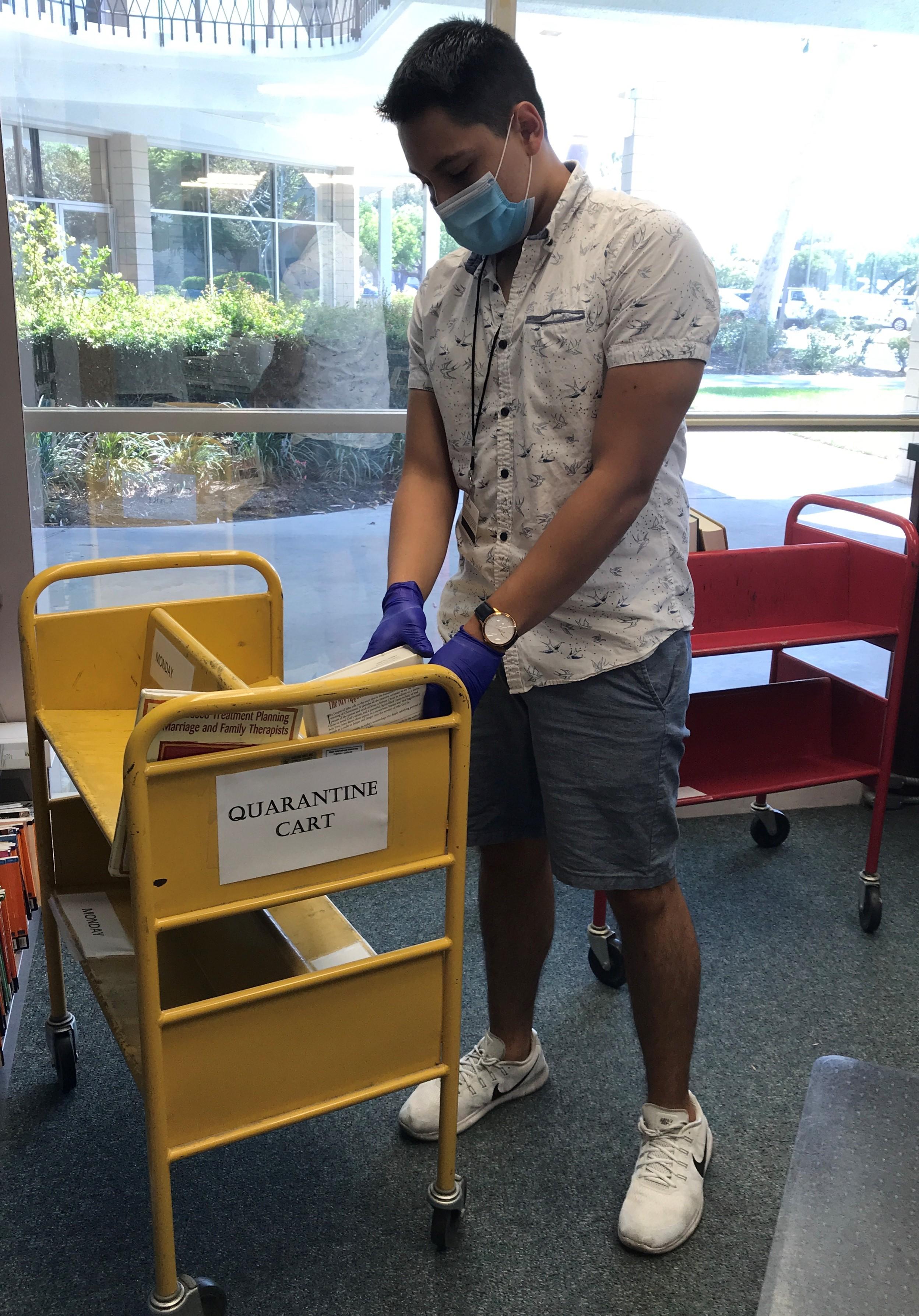 library staff putting book on quarantine cart