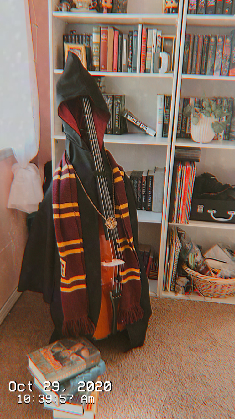 Cello with black robe and striped scarf like Harry Potter