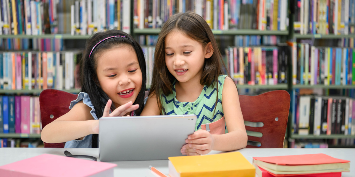 two children looking at a tablet and surrounded by books