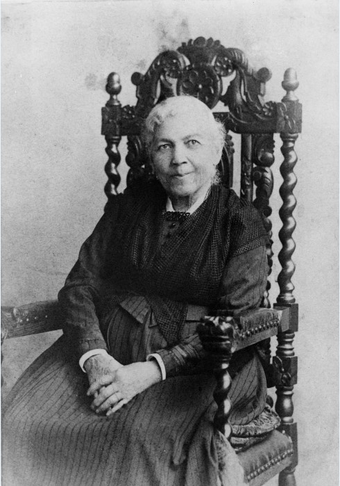 black and white photo of African American woman with black dress and white hair seated in ornate carved wooden chair