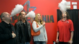 People blow vapor from e-cigarettes