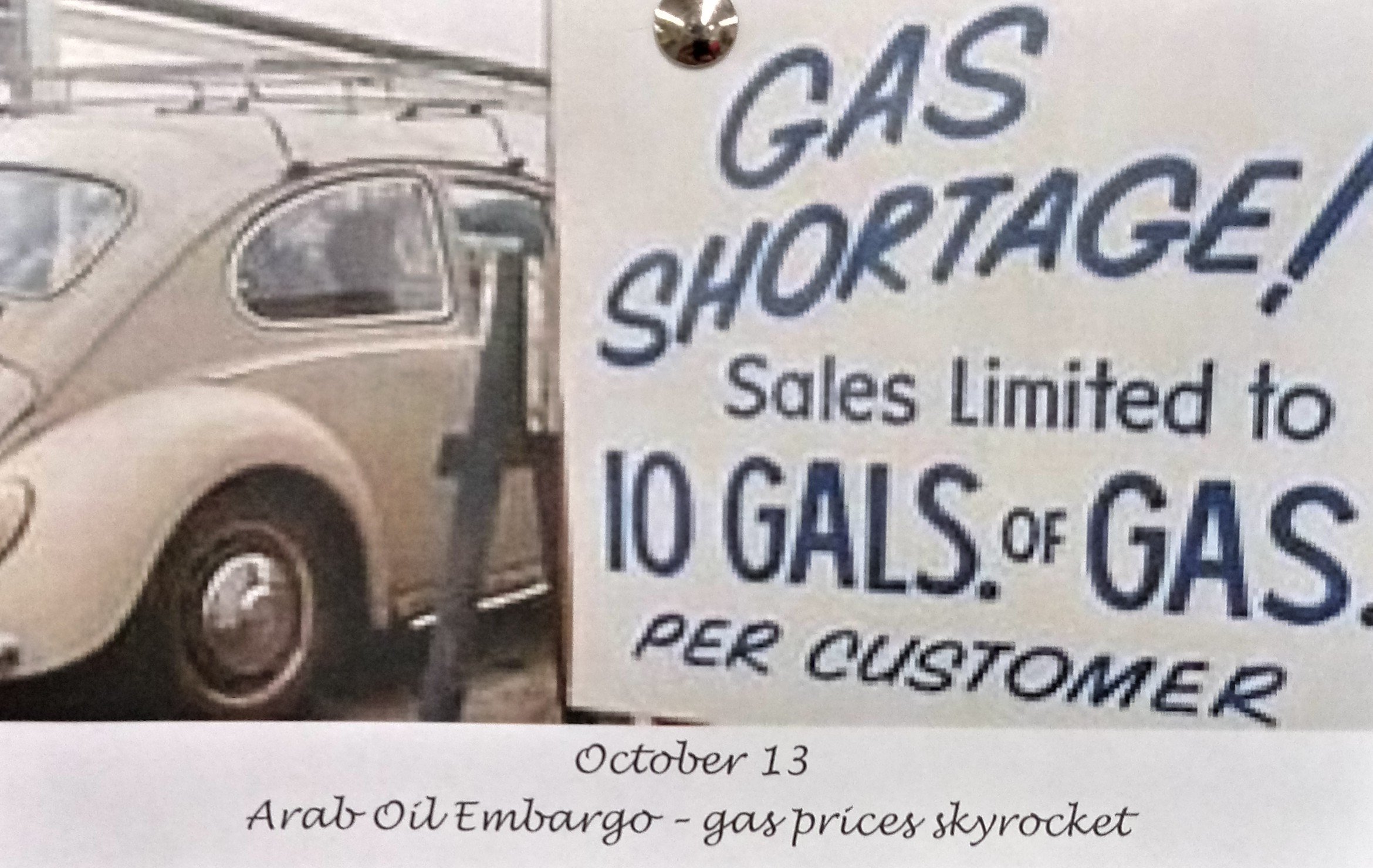 """Photograph of a sign posted at a gas station next to a Volkswagon Beetle car. Sign reads: """"Gas Shortage! Sales limited to 10 GALS. of GAS PER CUSTOMER""""."""