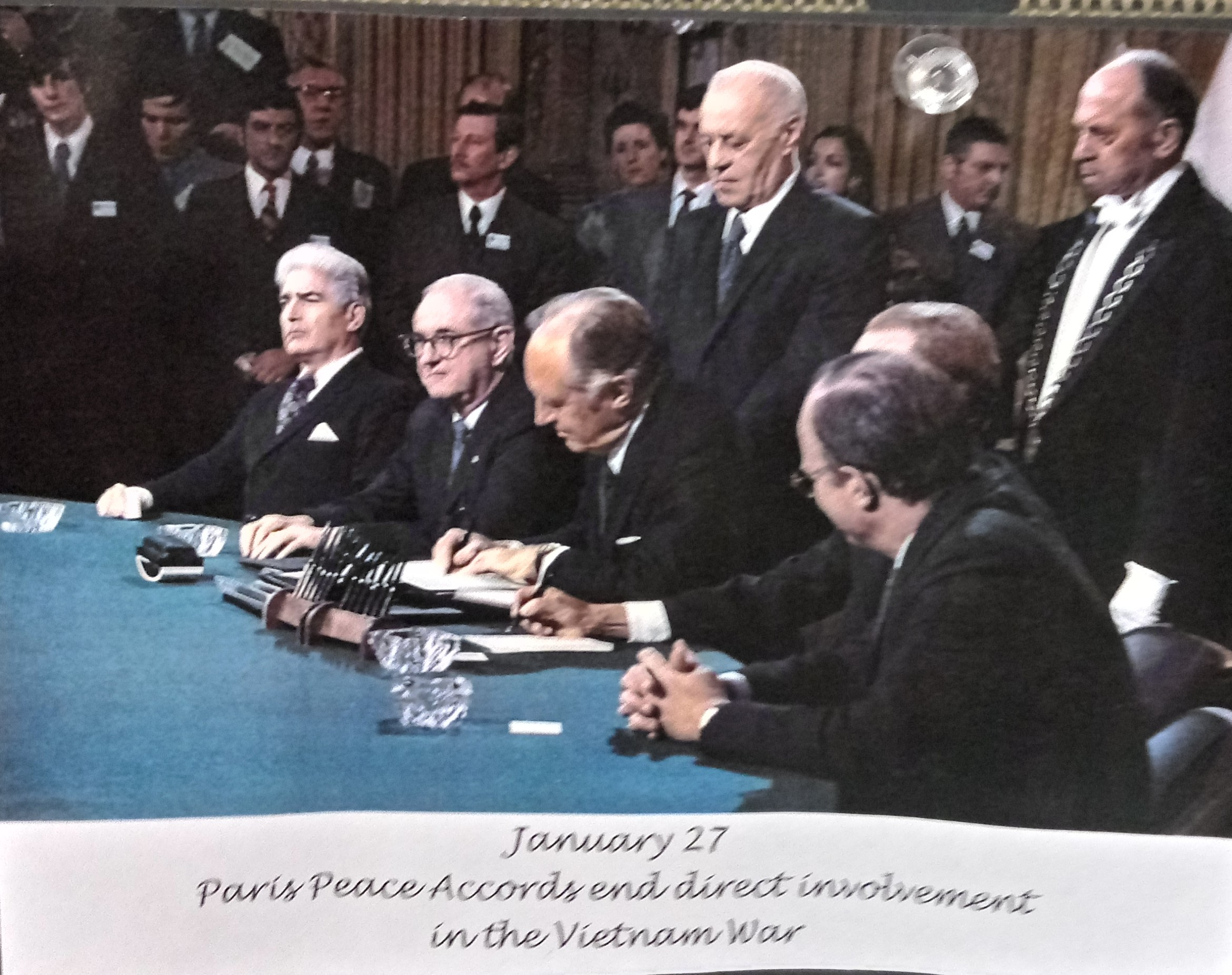 [Photograph of diplomats at a table, one of them signing a document.