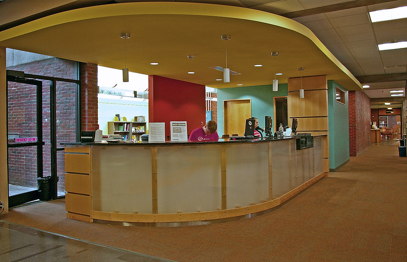 Photograph of the library circulation counter. A long counter that curves at one end.