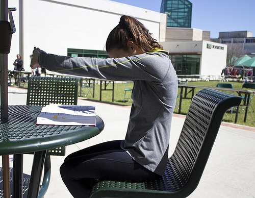 student stretching her arms and back while studying