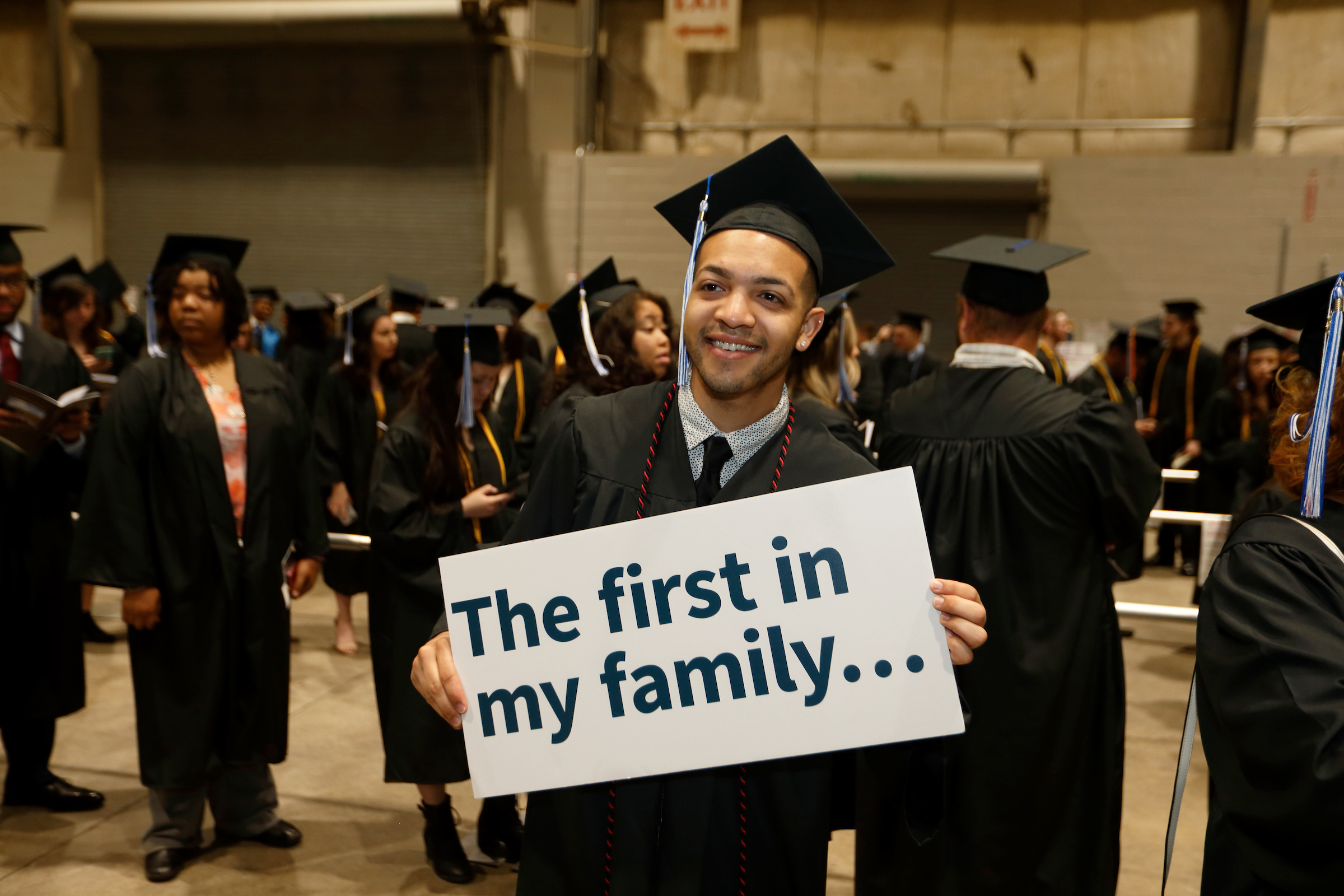 a person at their graduation holding a sign that says 'the first in my family...'