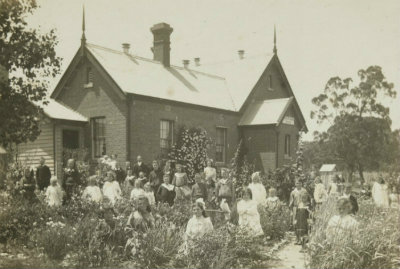 Photograph, Pupils and staff standing out front of Redcastle State School, No. 1655, in school garden H26444