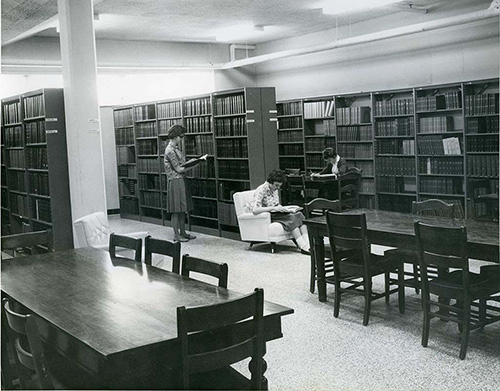 Library book shelves and study space in the lower level of Regina Hall