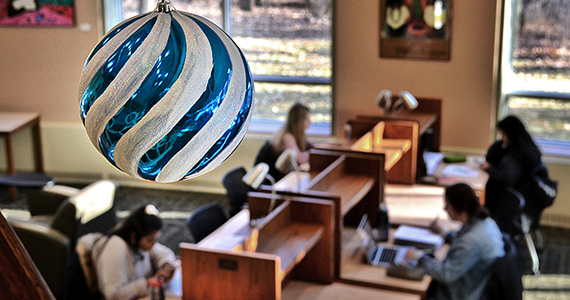 Christmas ornament hanging with students studying in the background