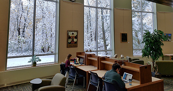 Two students study in front of windows showing a snowy scene outside