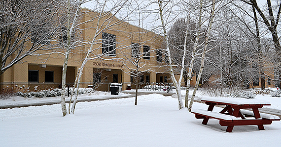 Front facade of the library with the ground and picnic table covered with snow