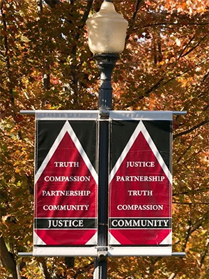 Two signs on a lamppost highlighting the Edgewood values of Justice and Community