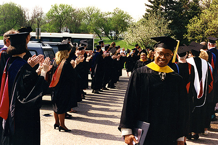 Graduate walking through a line of faculty applauding
