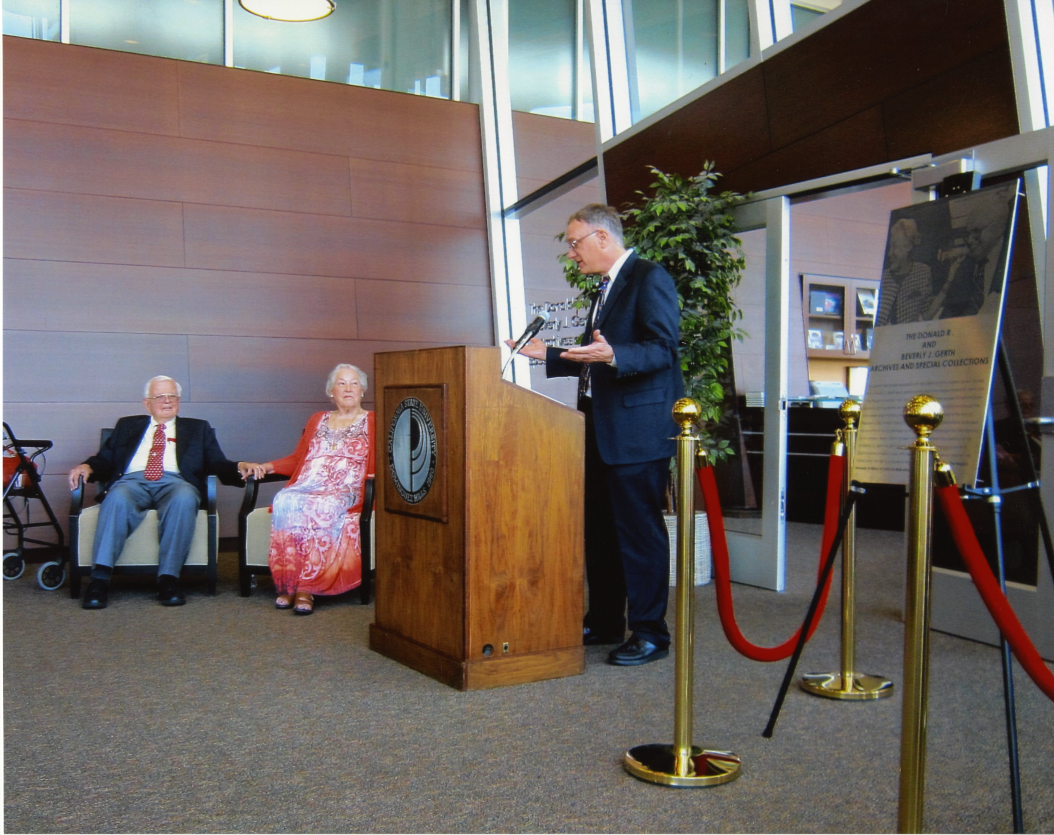 Greg Williams at podium, Donald and Beverly Gerth sitting, photograph