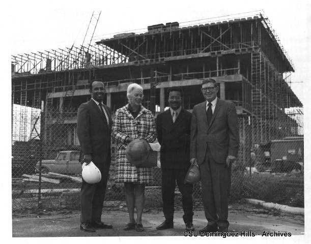 four individuals in front of library construction site in 1971